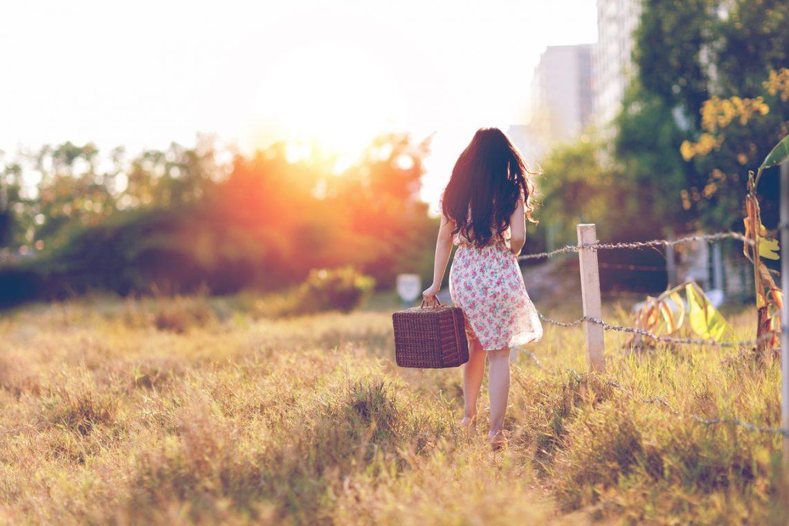 femme avec valise dans un champ